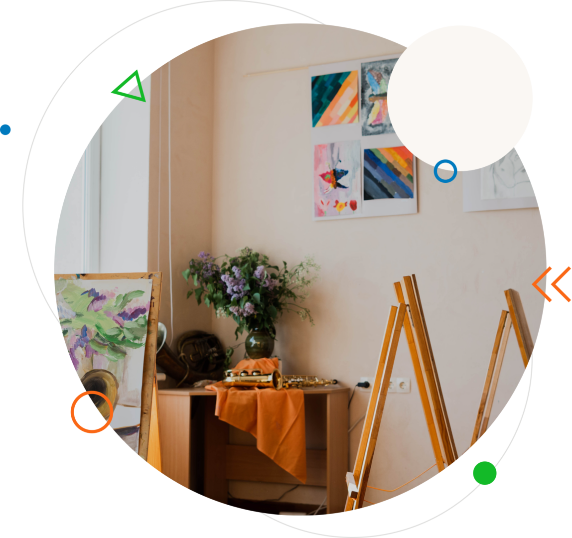 Mākslas studija ar molbertiem, kur centrā ir uzstādijums ar vāzi un ziediem. Blakus vāzei ir divi mūzikas instrumenti.